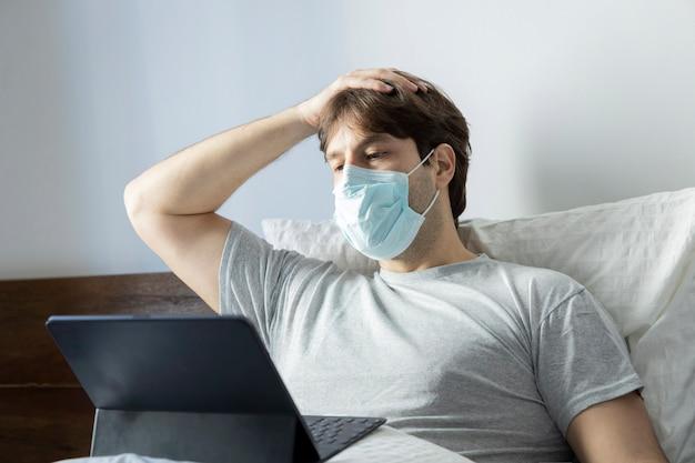 Человек работает в постели, делает домашний офис, потому что он болен. нанесение маски на рот и нос.