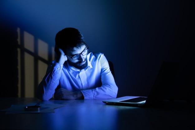 밤에 컴퓨터에서 작업하는 남자