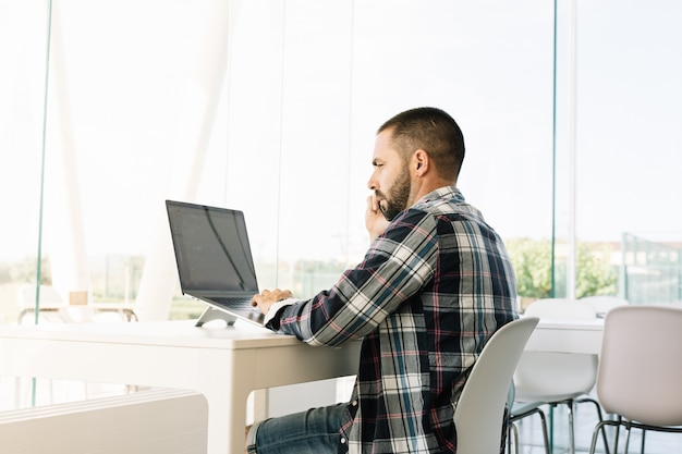 ノートパソコンの前で作業し、ワークスペースで携帯電話に話す男