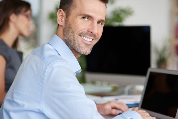 ラップトップで彼のオフィスで働いている男