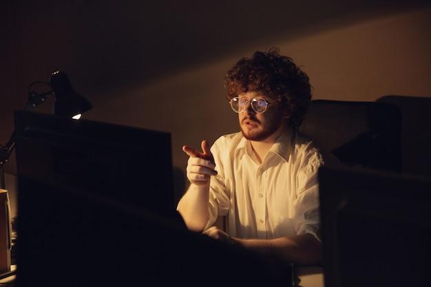 Человек, работающий в офисе один во время коронавируса или карантина covid-19, оставаясь до поздней ночи