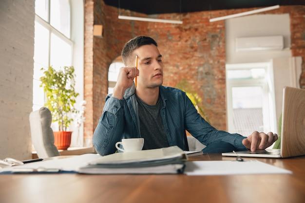 快適な服装、リラックスした姿勢、乱雑なテーブルでオフィスで働く男