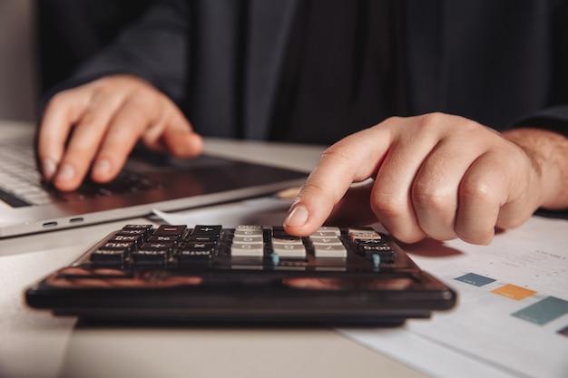 Человек, работающий в офисе с помощью калькулятора. бизнес-концепция. крупный план