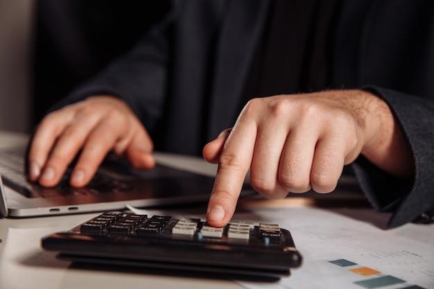 Человек, работающий в офисе с помощью калькулятора