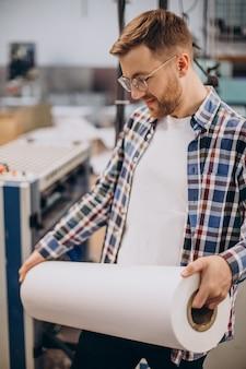 Человек, работающий в типографии с бумагой и красками