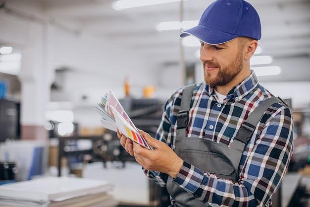 紙と塗料で印刷所で働く男