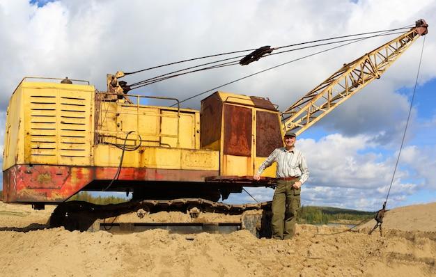 Человек, работающий в кране на песчаном карьере