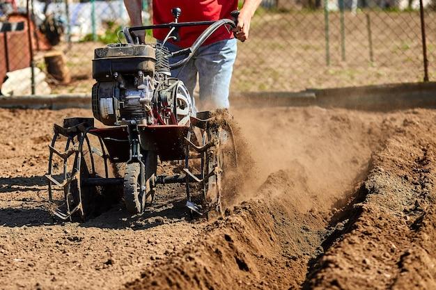 ガーデンティラーと一緒に庭で働く男。作業する庭の耕うん機、クローズアップ。