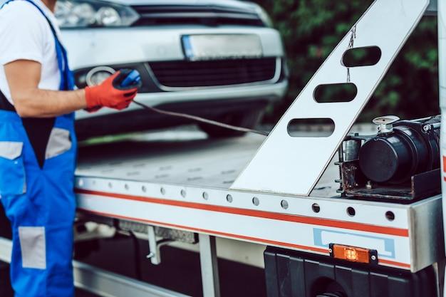 Человек, работающий в службе буксировки на дороге. концепция помощи на дороге.