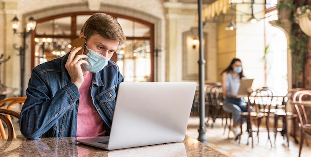 Uomo che lavora al chiuso mentre indossa una maschera per il viso con copia spazio