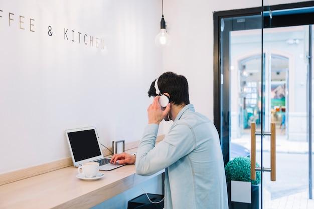 Man working at laptop in cafe