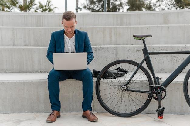 Uomo che lavora al computer portatile accanto alla sua bici all'esterno