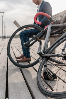 Uomo che lavora al computer portatile accanto alla sua bici