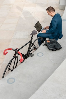 Man working on laptop next to his bike