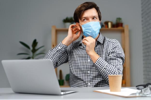 Man working on laptop at home and wearing medical mask close up