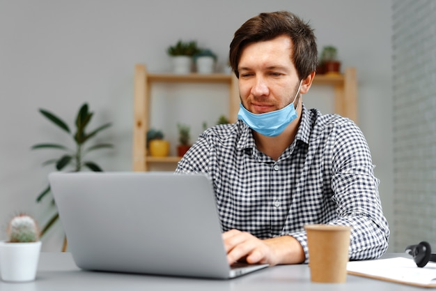 Man working on laptop at home and wearing medical mask