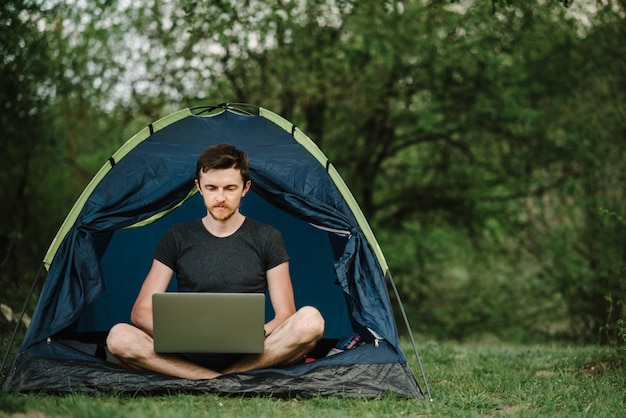 Man working on laptop in tent in forest, meadow