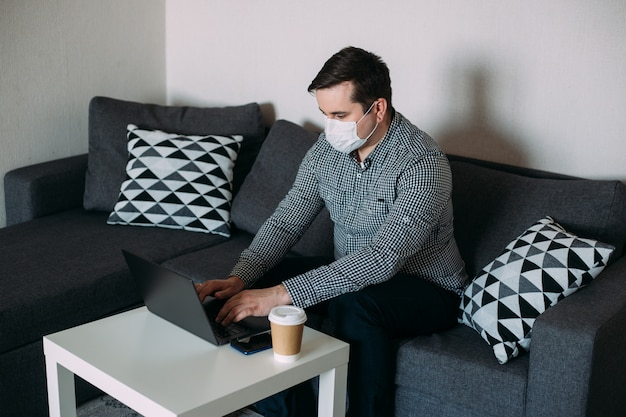 Man working on laptop wearing mask from home office