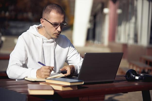 ノートパソコンで作業し、ノートに書いている男