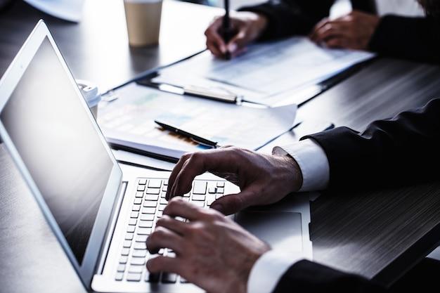 オフィスでラップトップに取り組んでいる男。インターネットの共有と相互接続の概念