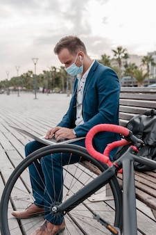그의 자전거 옆에 노트북에서 일하는 남자