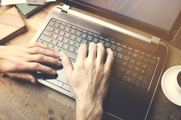 나무 테이블에서 노트북 작업을 하는 남자