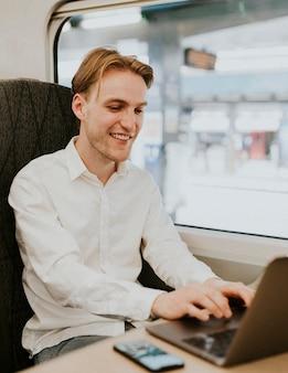 電車の中で彼の出張でラップトップに取り組んでいる男