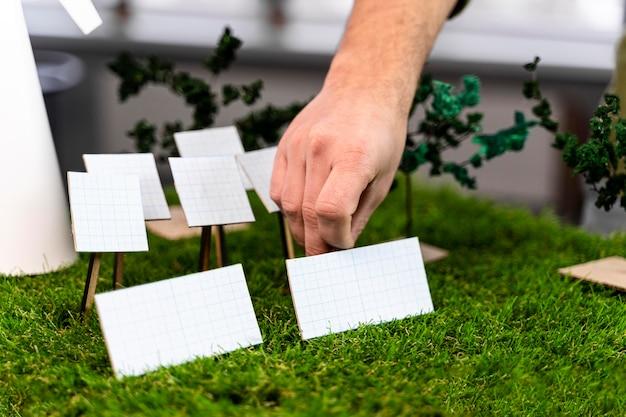 Человек, работающий над проектом экологически чистой энергии ветра с макетом