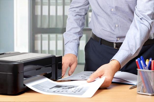 チャートやデータ、グラフ分析に取り組んでいる男性。ビジネスマンは監視のために文書を印刷します。