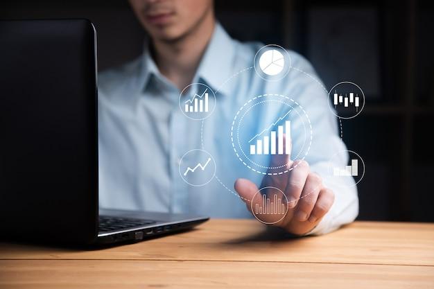 Человек, работающий на компьютере с трогательным успешным фондовым рынком с ростом