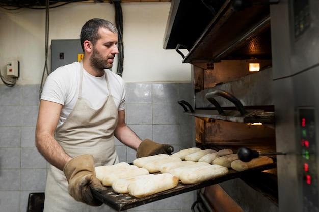 おいしい焼きたてのパンに取り組んでいる男