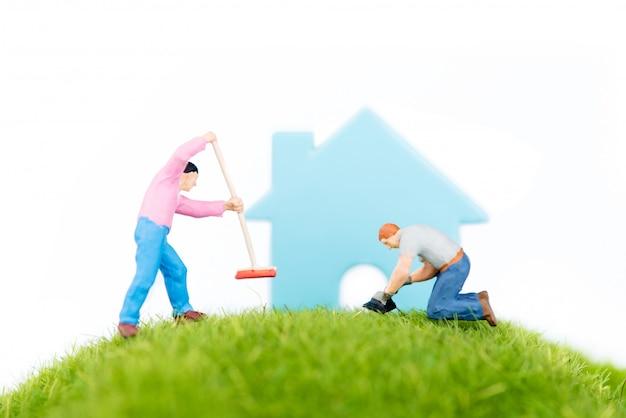 Человек, работающий на зеленой траве на дом
