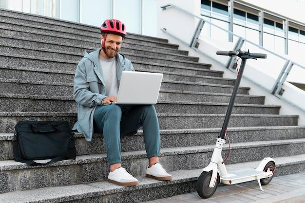 Человек, работающий на своем ноутбуке рядом со своим скутером