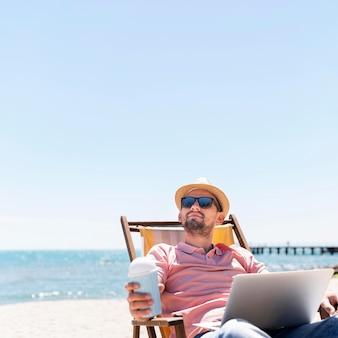 Человек работает на ноутбуке на пляже, наслаждаясь напитком