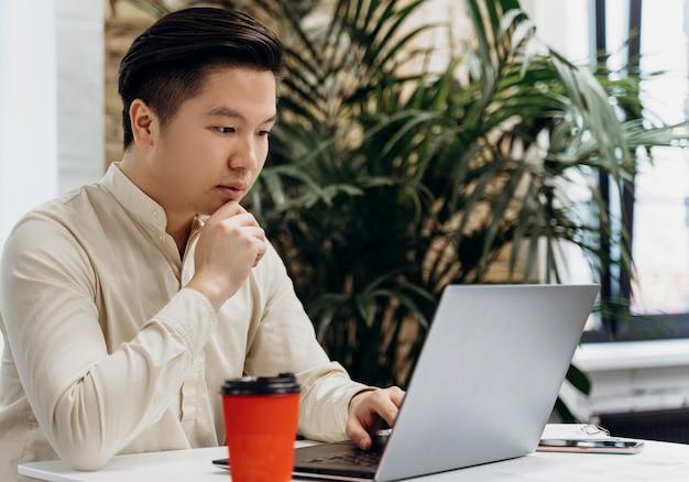 Человек, работающий на ноутбуке в офисе
