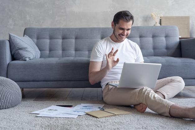 Человек, работающий на портативном компьютере, сидит на полу со своим дневником и официальными документами дома