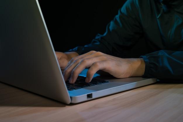 Человек, работающий на ноутбуке в темной комнате