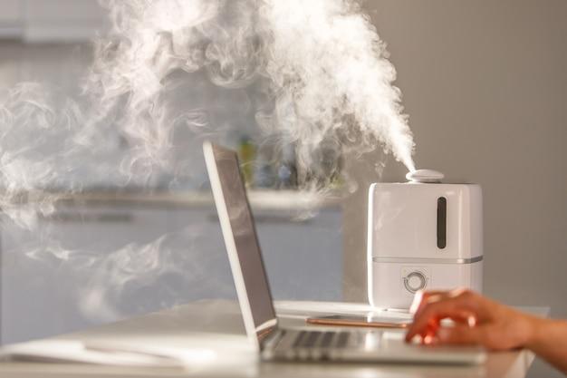 Человек работает на ноутбуке рядом с ароматом масла диффузора на столе, пар от увлажнителя воздуха, мягкий фокус