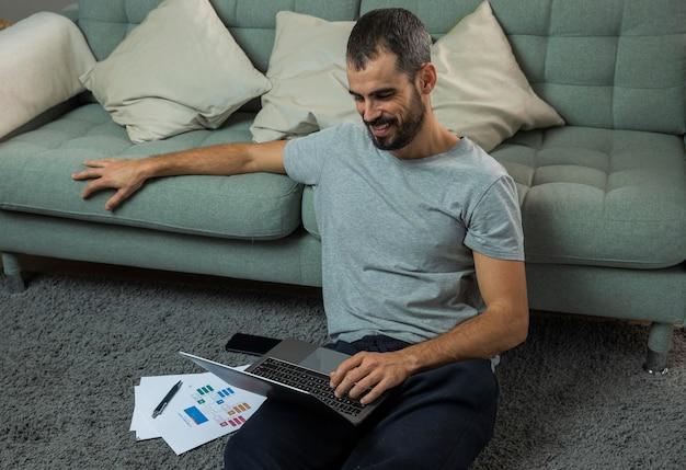 ソファの横にあるラップトップで作業している男