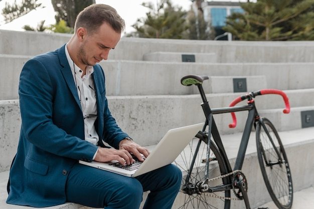 야외에서 그의 자전거 옆에 노트북에서 일하는 남자