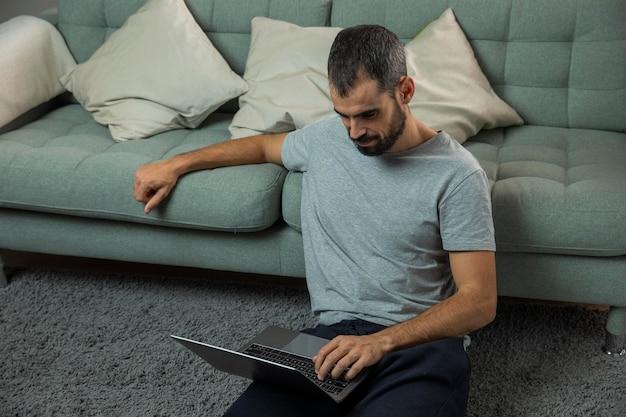 Человек, работающий на ноутбуке рядом с диваном