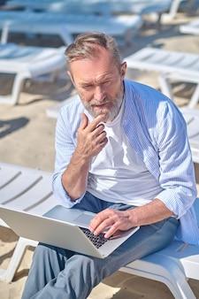 Человек, работающий на ноутбуке, сидя на открытом воздухе, думая