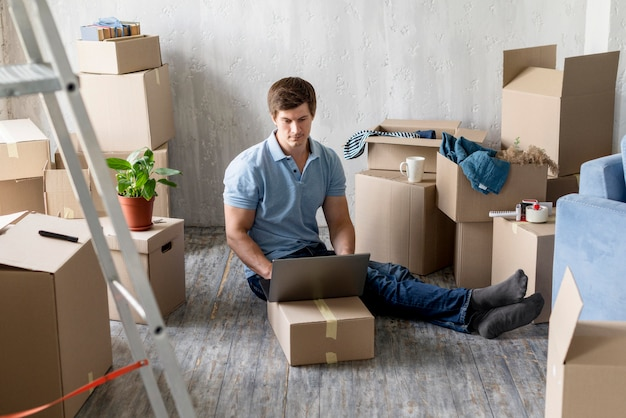 Человек, работающий на ноутбуке с коробками, готовыми к выезду