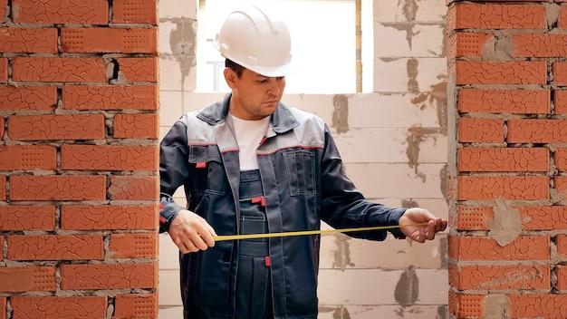 집을 짓고 테이프로 벽돌 벽의 출입구 너비를 측정하는 현장에서 일하는 남자