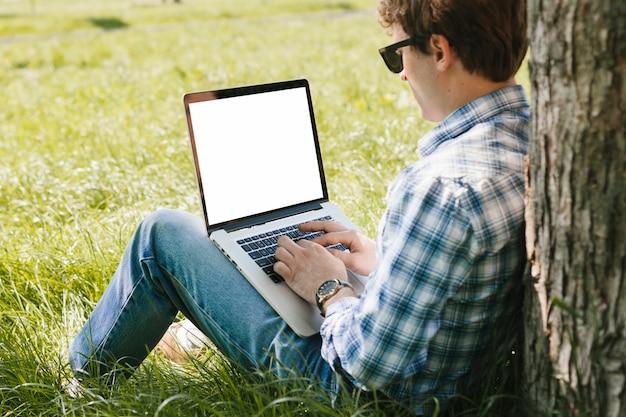 男は公園でラップトップに取り組んで 無料写真