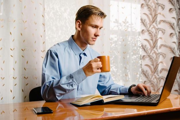自宅からノートパソコンでオンラインで作業し、自宅でコーヒーを飲む男性。自宅でラップトップを使用してビジネスマン。