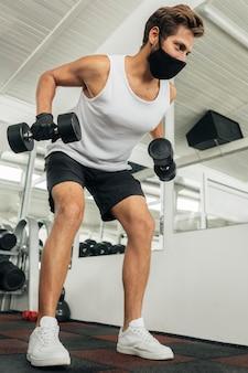 의료 마스크를 착용하는 동안 체육관에서 운동하는 남자