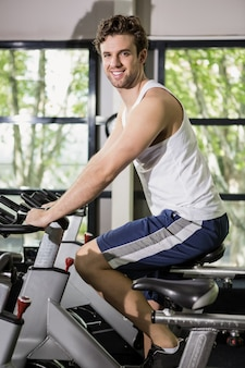 Man working out on exercise bike at spinning class