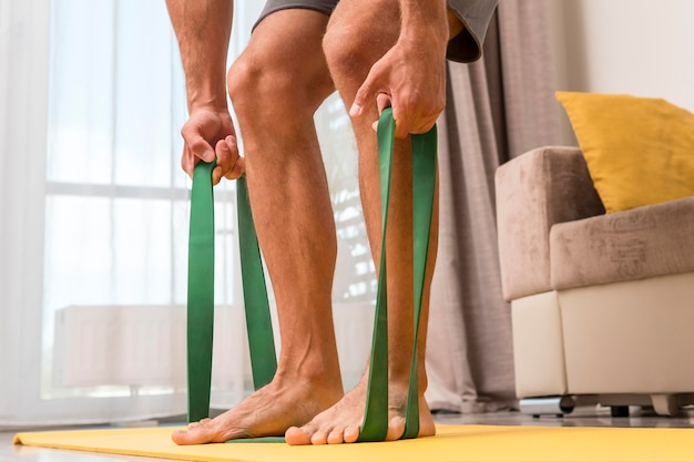 Man working out at home using elastic band