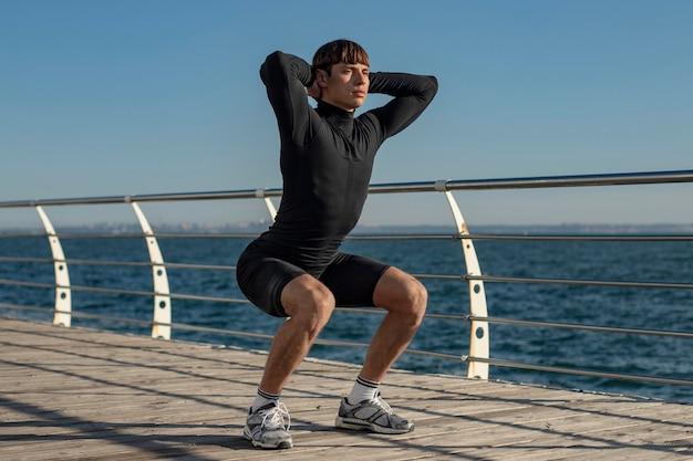 Мужчина работает в спортивной одежде на пляже